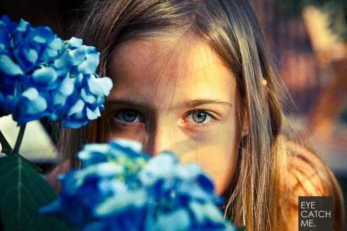 Der Kinder Fotograf aus Köln macht professionelle Kinderfotos, dass Foto Zeigt ein Mädchen Portrait welches hinter einer schönen Blume sitzt